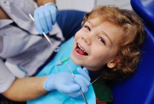 Male Dentist Examines A Young Patient